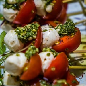 Cherry tomatoes with mozzarella pearls and pesto dressing